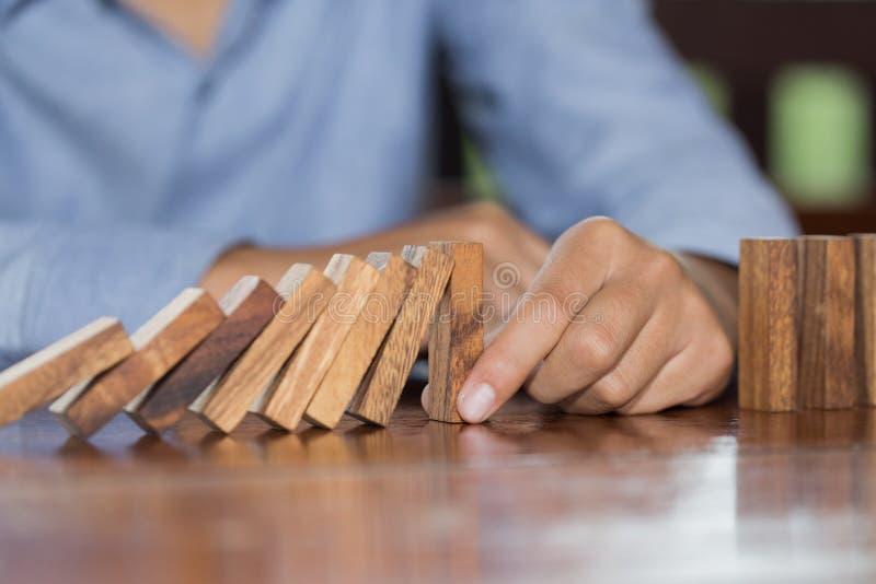 Biznesmen ręki powstrzymywania domin spada drewniany skutek od ciągły przewracać się, ryzyko, strategia lub pomyślna interwencja, obrazy stock
