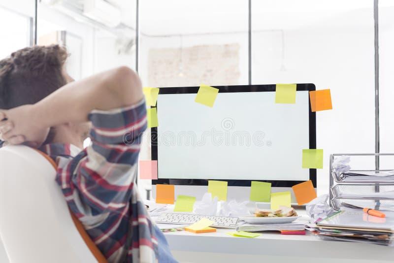 Biznesmen relaksuje przed komputerem z pustym ekranem w biurze fotografia royalty free