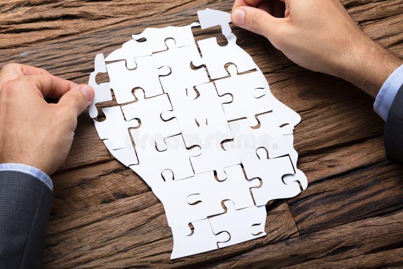 Biznesmen Robi głowie Od Papierowych wyrzynarki łamigłówki kawałków Na stole obrazy royalty free