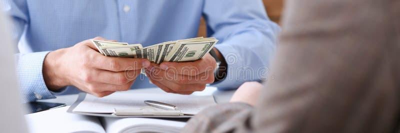 Biznesmen rozważa gotówkowych dolary w biurze zdjęcie stock