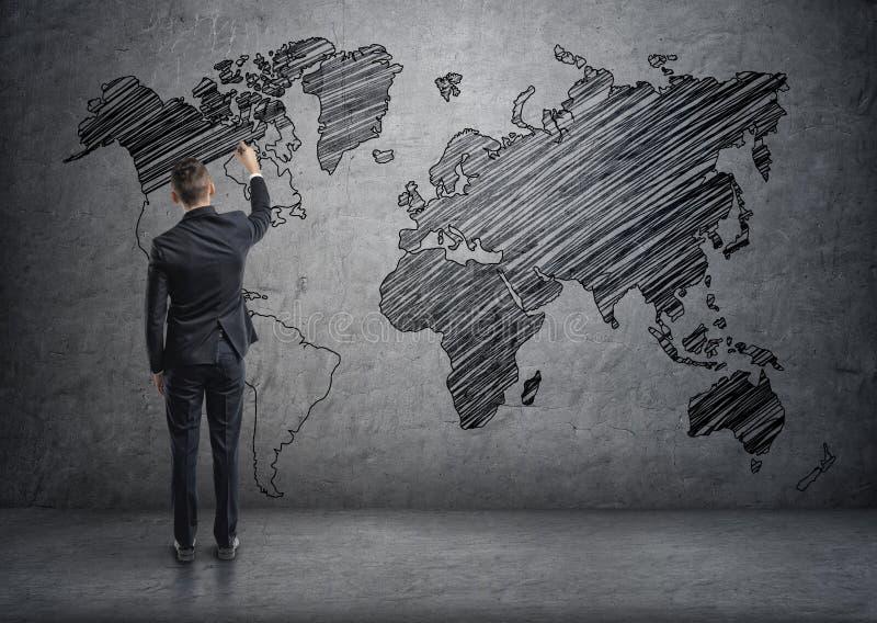 Biznesmen rysuje światową mapę na betonowej ścianie fotografia stock