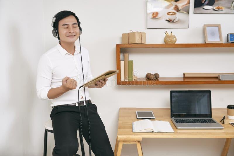 Biznesmen słucha muzyka przy biurem fotografia stock