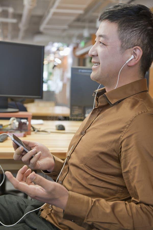 Biznesmen Słuchająca muzyka w ono Uśmiecha się i biurze obrazy royalty free