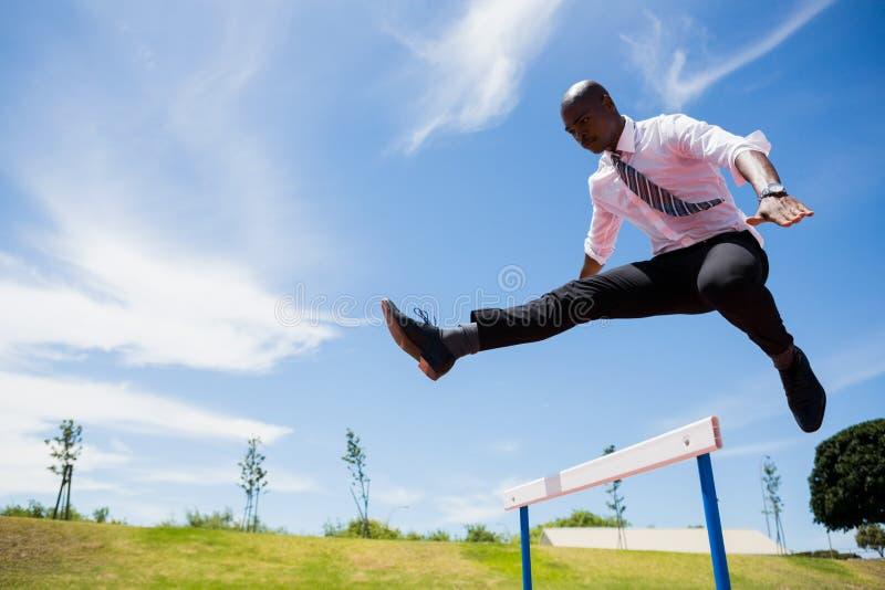 Biznesmen skacze przeszkodę podczas gdy biegający zdjęcia royalty free