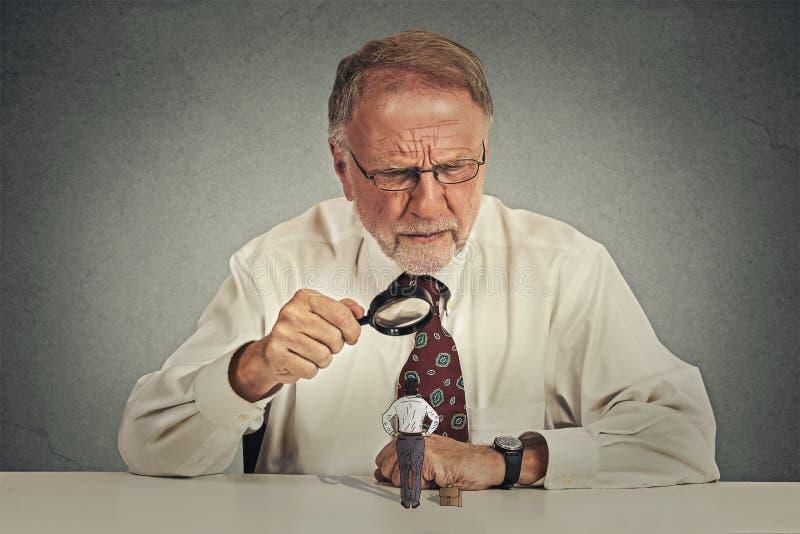 Biznesmen skeptically patrzeje małego pracownika przez powiększać - szkło fotografia stock