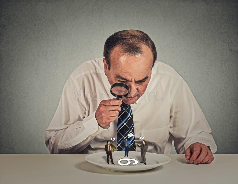 Biznesmen skeptically spotyka patrzejący małego pracownika fotografia royalty free