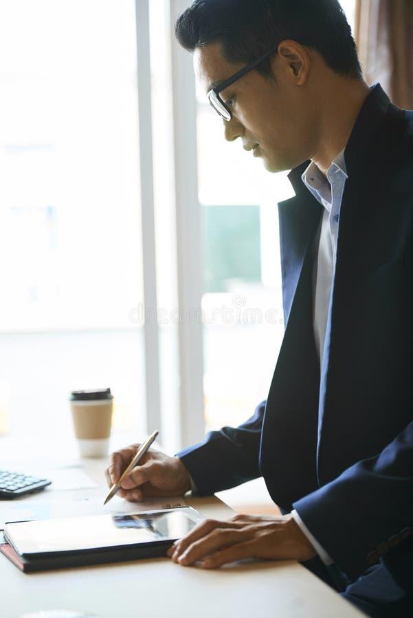 Biznesmen sprawdza dokument na pastylka komputerze obraz royalty free