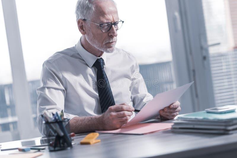 Biznesmen sprawdza dokument zdjęcia royalty free