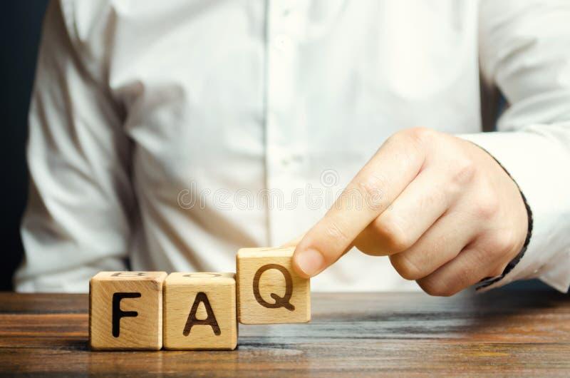 Biznesmen stawia drewnianych bloki z słowa FAQ dobrowolnie pytać pytaniami Kolekcja dobrowolnie pytać pytania na żadny zdjęcie stock