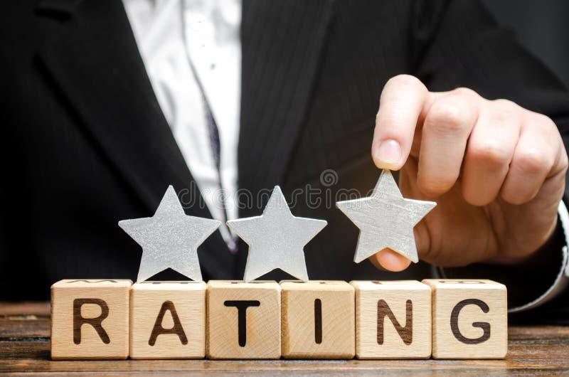 Biznesmen stawia trzeci gwiazdę nad słowo ocena na drewnianych blokach Pojęcie ilość usługa Hotel lub restauracja obraz royalty free