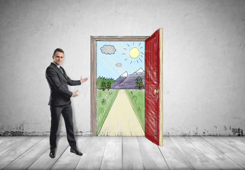 Biznesmen stoi pokazywać pogodną scenę z górami za otwarte drzwi i drogą oba rękami zdjęcia stock