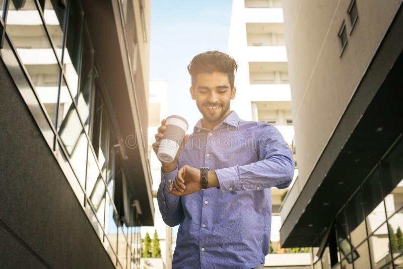 Biznesmen synkliny chodząca ulica sprawdza czas obrazy stock