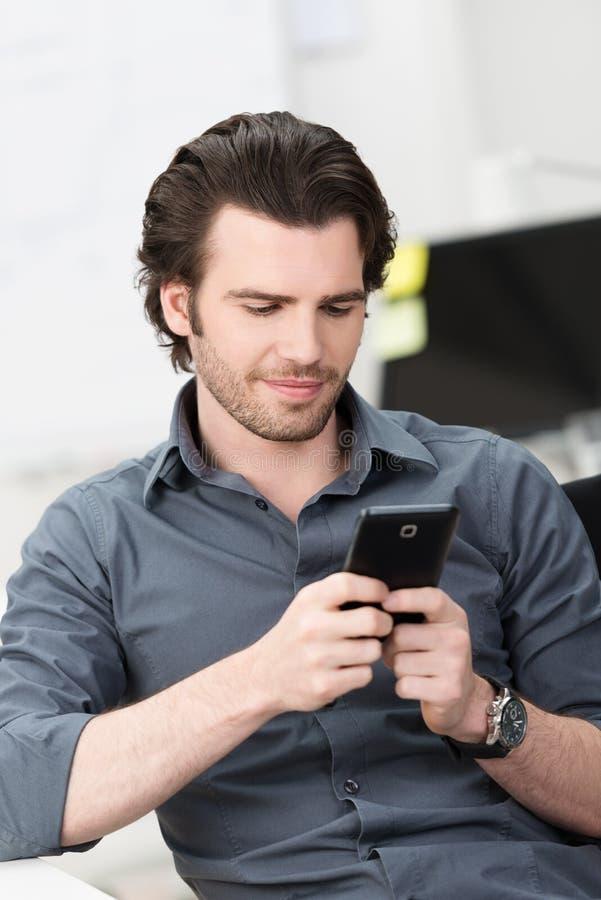 Biznesmen texting na jego telefonie komórkowym obrazy stock