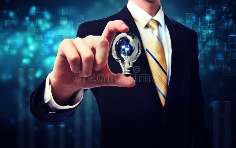 Biznesmen trzyma żarówkę zdjęcia stock