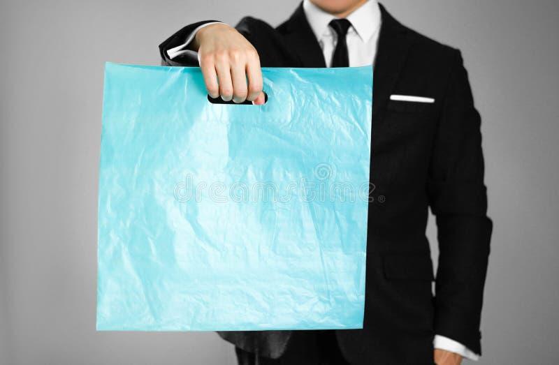 Biznesmen trzyma błękitnego plastikowego worek w czarnym kostiumu z bliska Odosobniony tło obrazy stock