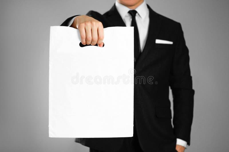 Biznesmen trzyma białego plastikowego worek w czarnym kostiumu z bliska Odosobniony tło zdjęcia stock