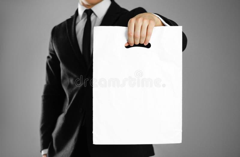 Biznesmen trzyma białego plastikowego worek w czarnym kostiumu z bliska Tło obrazy stock