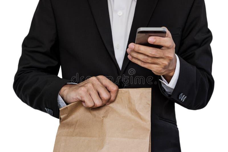 Biznesmen trzyma brown papierową torbę i używa mądrze telefon, odizolowywającego na białym tle obrazy stock