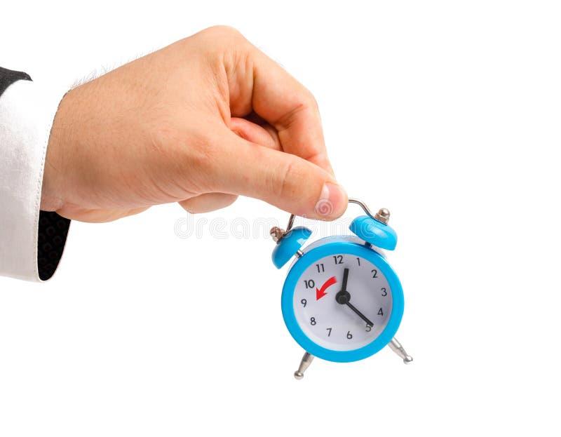 Biznesmen trzyma budzika Przemiana zima czas, przeniesienie godziny godzina z powrotem Zegarek w ręce przeciw jako tła popasu poj obrazy stock