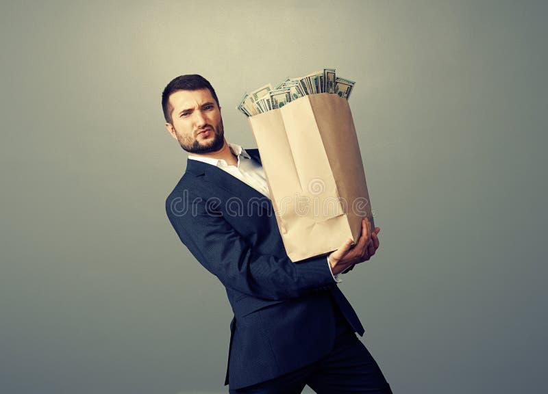 Biznesmen trzyma ciężką papierową torbę zdjęcia stock