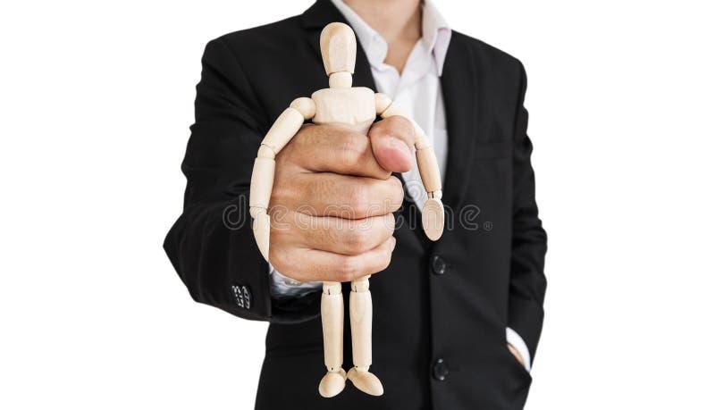 Biznesmen trzyma drewnianą postać, pojęcie bierze kontrola, ciemięży, i etc , odizolowywający zdjęcie stock