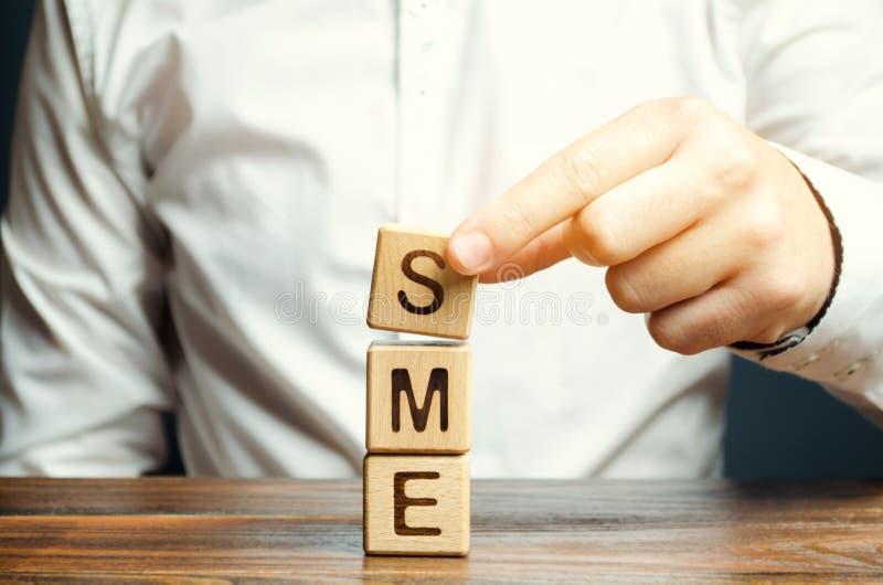 Biznesmen trzyma drewnianych bloki z słowem SME Małych i średnich rozmiarów przedsięwzięcia - handlowi przedsięwzięcia które no p zdjęcia royalty free