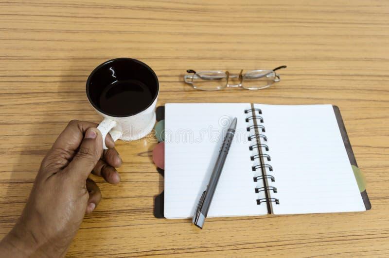 Biznesmen trzyma filiżankę kawy Biznesu kieszeniowy planista z eyeglass i piórem gotowymi zauważać spotkanie Biznes zdjęcia royalty free
