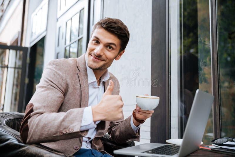 Biznesmen trzyma filiżankę kawy i działanie z laptopem outdoors zdjęcia royalty free