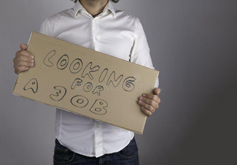 Biznesmen trzyma inskrypcję - Patrzejący dla pracy obraz royalty free