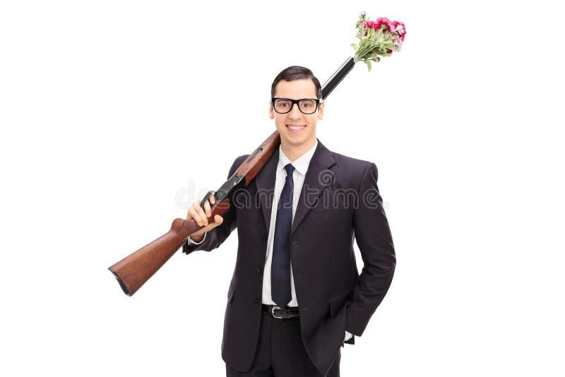 Biznesmen trzyma karabin ładujący z kwiatami zdjęcia stock