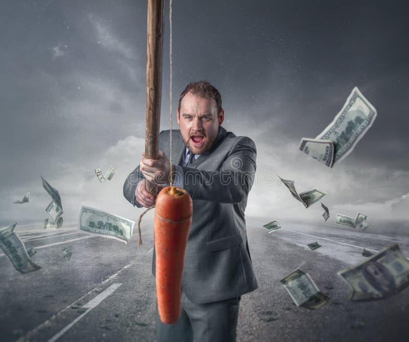 Biznesmen trzyma marchewki w kiju zdjęcia stock