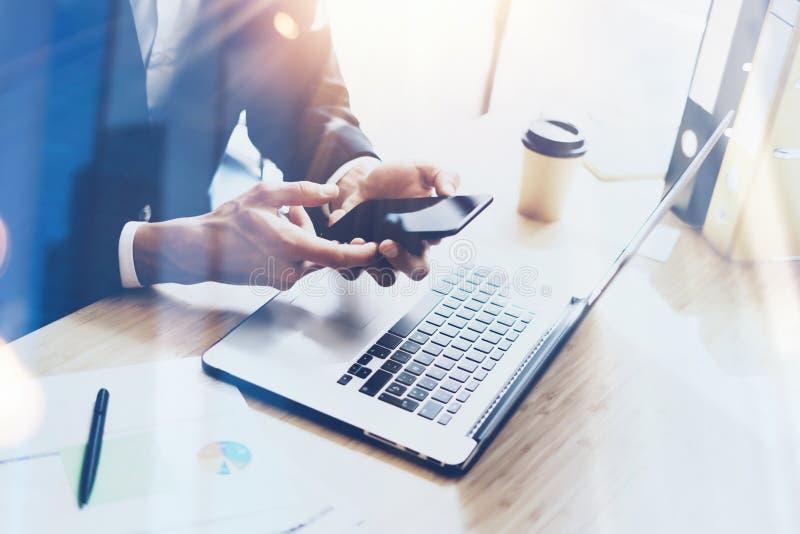 Biznesmen trzyma nowożytnego smartphone na rękach Coworker pracuje przy pogodnym biurem przy miejscem pracy Wizualni skutki zamaz obraz royalty free