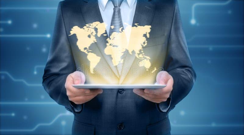 Biznesmen trzyma pastylka komputer osobistego komputerowy z projekcyjnym ekranem graficzna światowa mapa fotografia stock