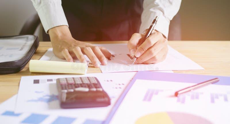 Biznesmen trzyma pióro i pisze raportach wykres pokazuje z zmierzchem zdjęcia royalty free