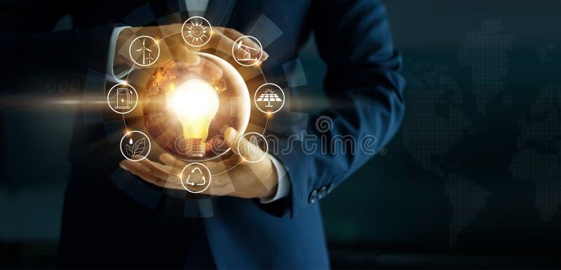 Biznesmen trzyma rozjarzoną żarówkę z energetycznych źródeł ikoną fotografia stock