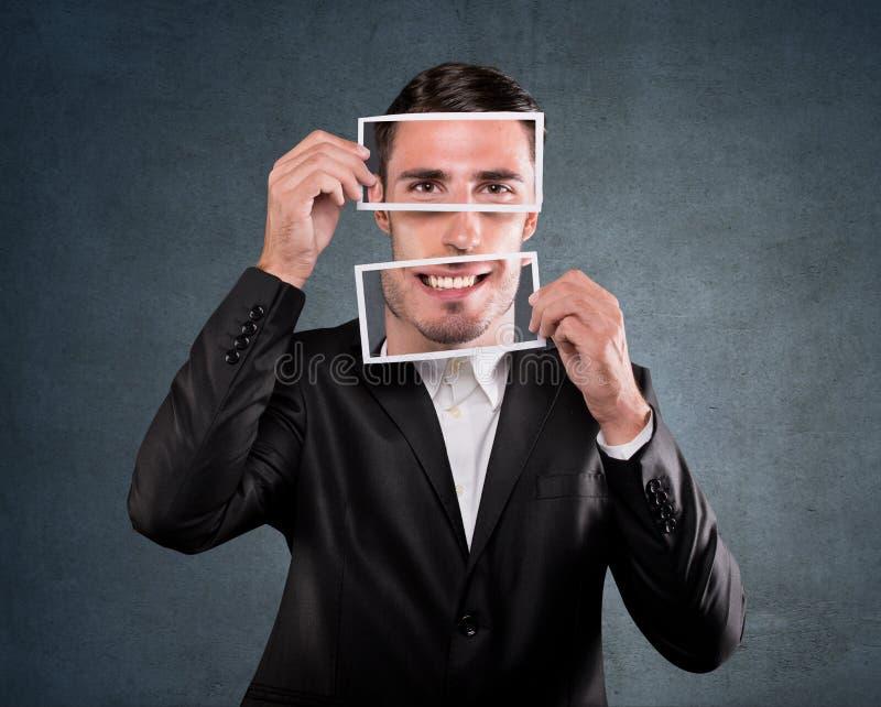 Biznesmen trzyma uśmiech nad jego twarzą obrazy royalty free