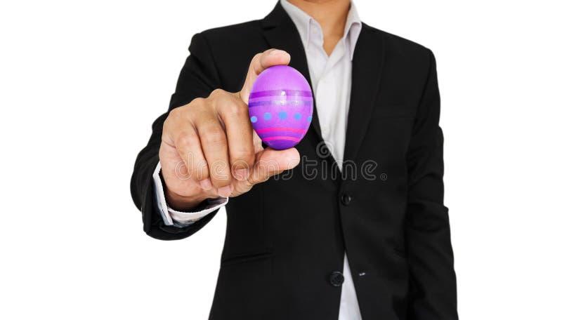 Biznesmen trzyma Wielkanocnego jajko, odizolowywającego na białym tle zdjęcie royalty free