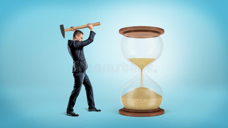 Biznesmen trzyma wielki ciężki młoteczkowego przygotowywa uderzać wielkiego hourglass z połówką swój piasek spadać puszek zdjęcia stock