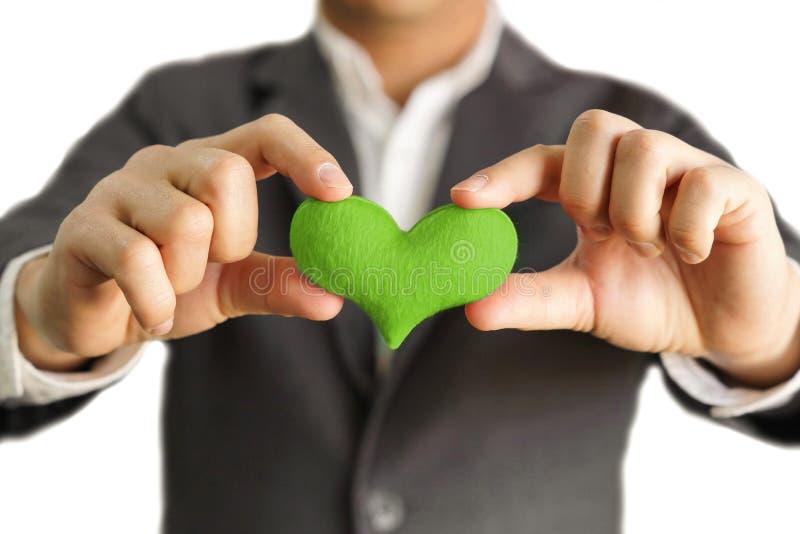 Biznesmen trzyma zielonego serce obraz royalty free