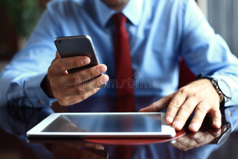 Biznesmen używa cyfrowego pastylka komputer z nowożytnym telefonem komórkowym Nowe technologie dla sukcesu obieg pojęcia obraz royalty free