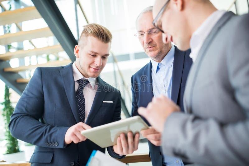 Biznesmen Używa Cyfrowej pastylkę Z kolegami W biurze obraz stock