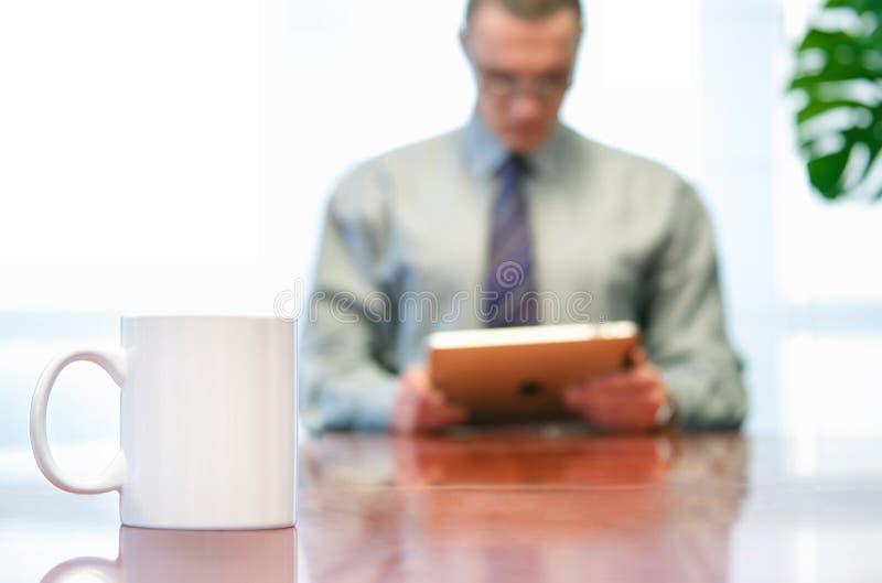 Biznesmen używa jego pastylkę w biurze obrazy stock