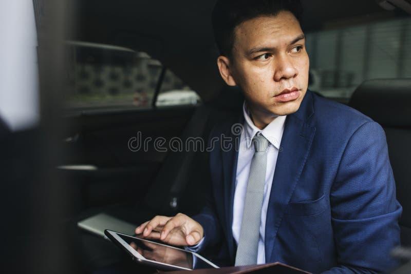 Biznesmen używa jego pastylkę w samochodzie obrazy royalty free