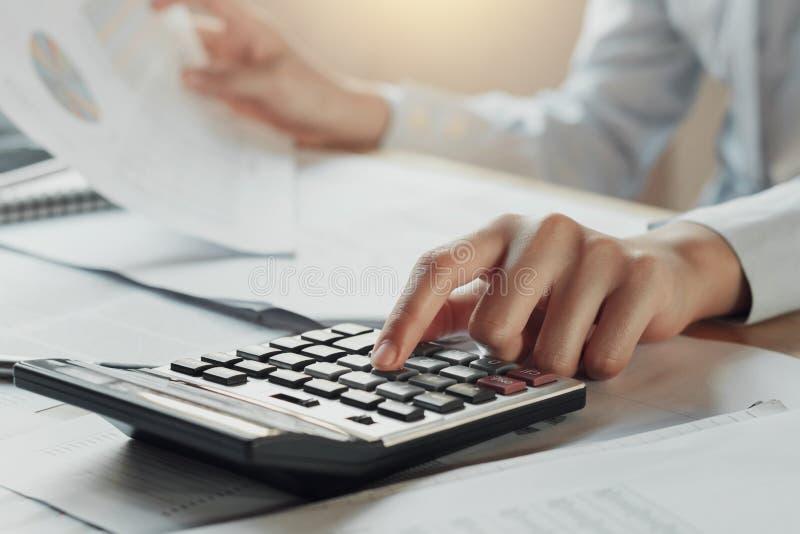biznesmen używa kalkulatora dla kalkuluje budżet na stole wewnątrz obrazy stock