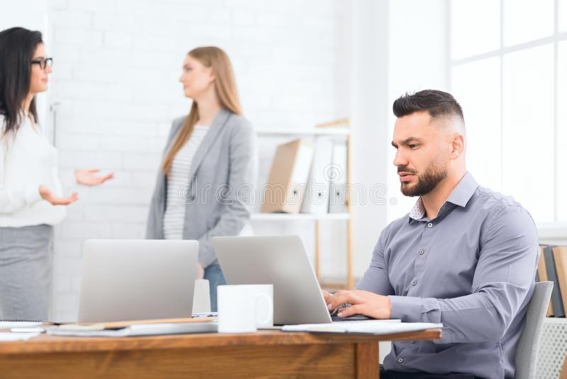 Biznesmen używa laptop podczas gdy coworkers oddziała wzajemnie na tle obrazy royalty free