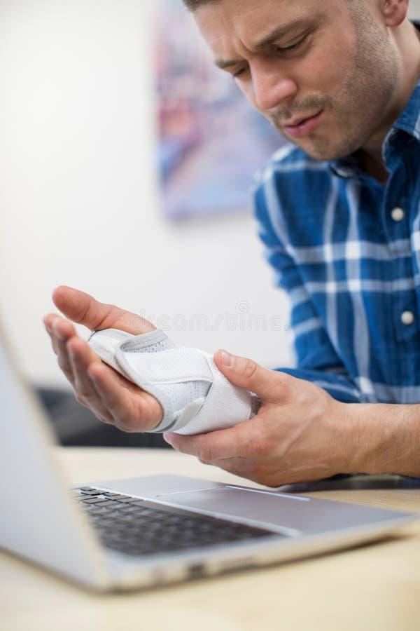Biznesmen Używa laptopu cierpienie Od Powtórkowego napięcia urazu zdjęcia royalty free