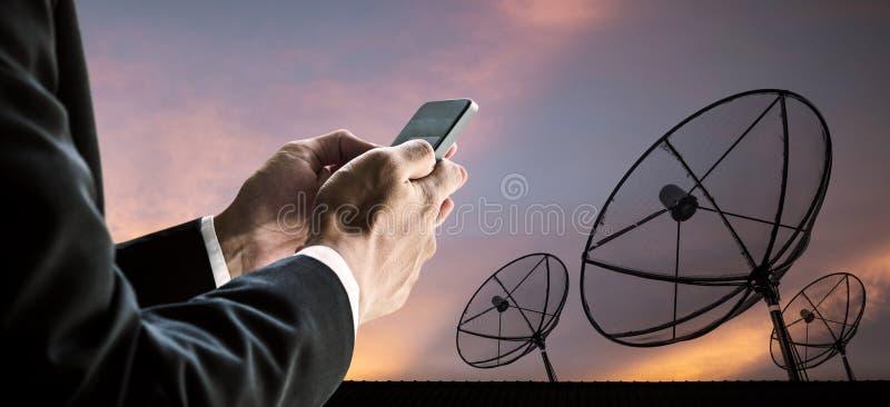 Biznesmen używa mądrze telefon z sylwetek telecoms anteny satelitarnej cyfrową siecią i zmierzchu niebem, obraz stock