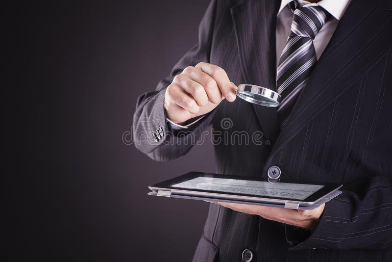 Biznesmen używa pastylka komputer z powiększać - szkło obrazy stock