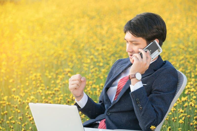 Biznesmen używa smartphone i laptop w kwiatu polu zdjęcie stock