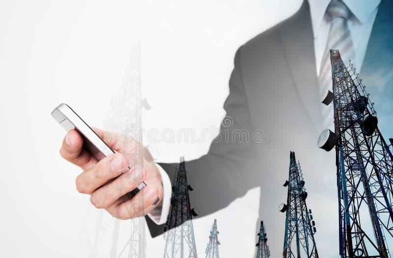 Biznesmen używa smartphone, z dwoistego ujawnienia telekomunikaci wierza obraz stock